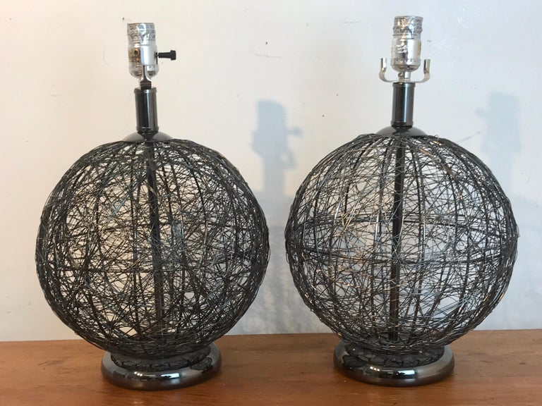 Pair of midcentury spun gun metal sphere lamps, each one of Kinetic form, raised on a 6