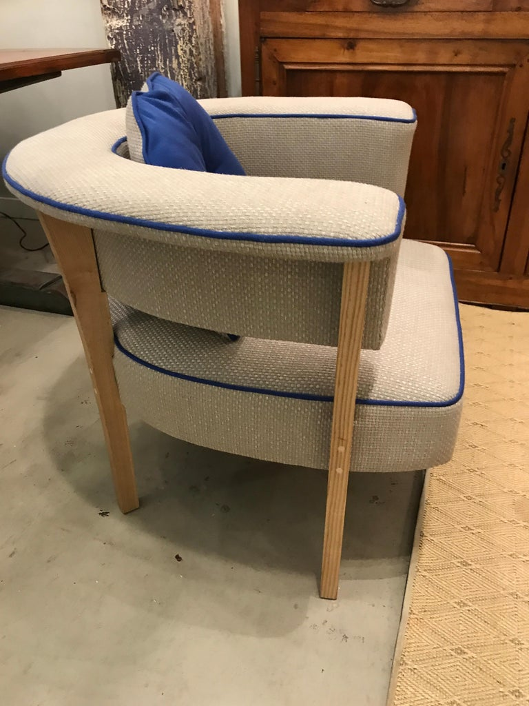 """Unusual pair of midcentury style modern armchairs. Styled after a 1960s Danish design. Called the """"Viking Chair"""" Upholstered in grey linen with blue piping, and with blue accent pillows. Extremely comfortable with horse shoe shaped arms over"""