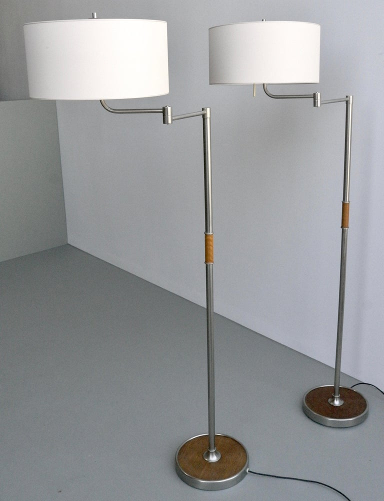 Pair of midcentury swing-arm floor lamps in metal with faux bamboo wood details.  Adjustable in many positions. Height 162cm, diameter base 30cm.