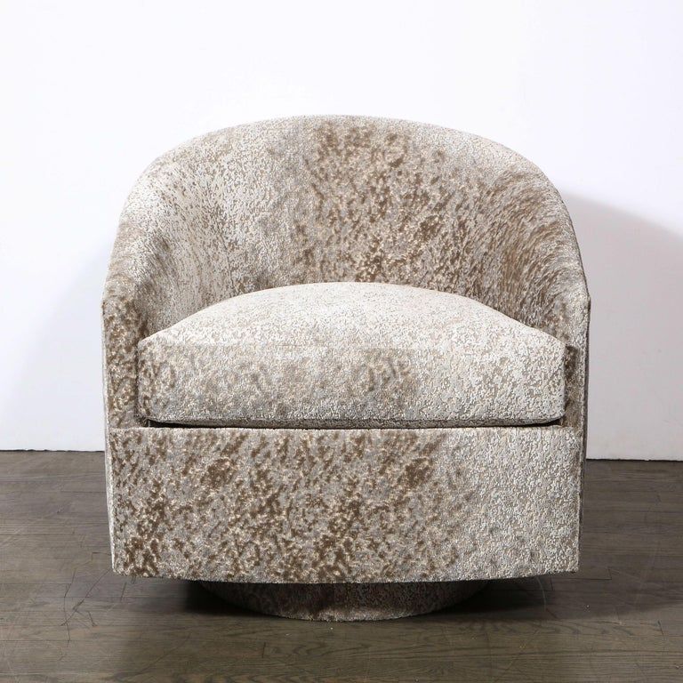 This stunning pair of Mid-Century Modern swivel lounge chairs were realized in the United States, circa 1970. They feature curvilinear barrel backs; circular bases; and gently sloped backs. The chairs have been newly reupholstered in Great Plains