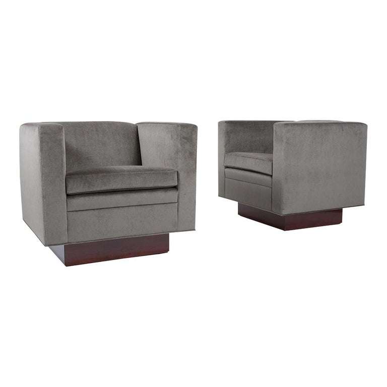 This Pair of Mid-Century Modern 1960s Swivel chairs have been professionally restored and features a sleek cube, flat back, and armrest design. These lounge chairs have been professionally upholstered in a new grey color mohair velvet fabric with