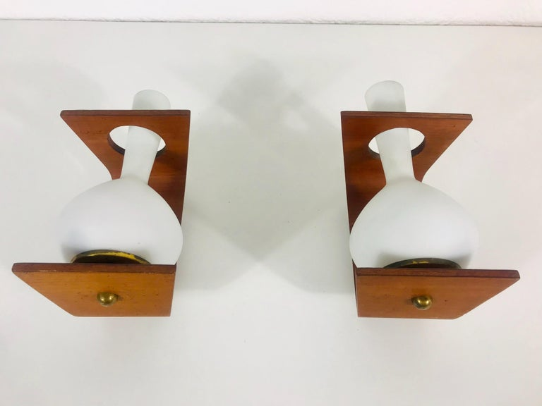 A pair of Italian wall lamps made in the 1960s attributed to Stilnovo. It is fascinating with its rare glass shape. The body of the lamp is beautiful teak wood. 