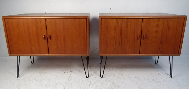 A beautiful pair of Danish teak cabinets that boast metal hairpin legs and sculpted pulls. A large compartment with a shelf offers plenty of room for storage. The rich teak finish and clean lines show quality craftsmanship. A lovely Mid-Century