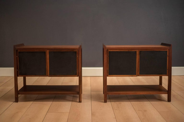 Mid-century modern pair of nightstands or end tables in walnut. This set features swing out doors lined with black vinyl that provides interior storage space. Also, includes a lower tier shelf. Matching high and lowboy dresser available in separate