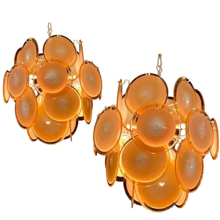 Each chandelier is formed by 24 honey discs of precious Murano glass are arranged on floor levels. Nine lights. Measures: Height without chain 50 cm. Available also with white and pink discs.