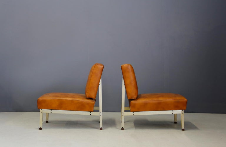 Pair of armchairs in the style of Florence Knoll from 1950. The armchairs have a steel frame inserted in a very linear way with clean and essential lines. Its seat and backrest cover is in light brown leather in perfect condition. In the back of the