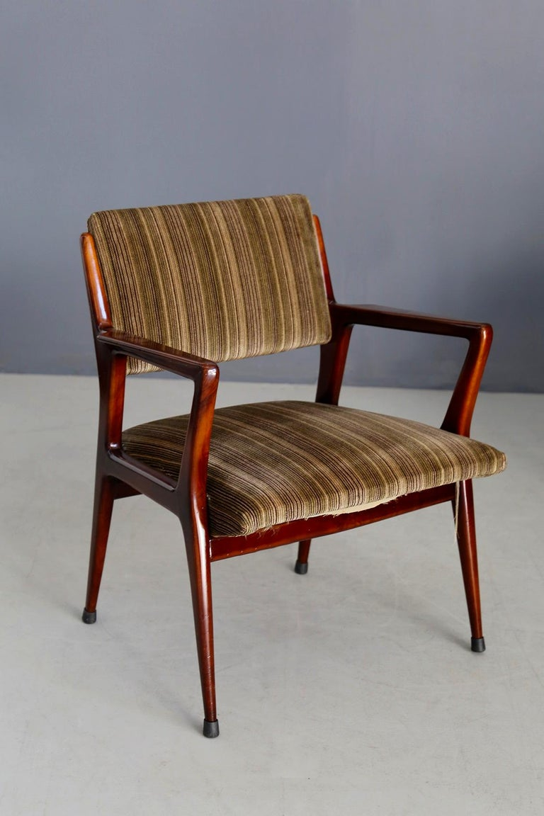 Pair of armchairs attributed to Gio Ponti in walnut wood. The armchairs have the original fabric of the time, a colored corduroy. The armchairs have been restored but have defects in its fabric and slight wear and tear. The pair is perfect to