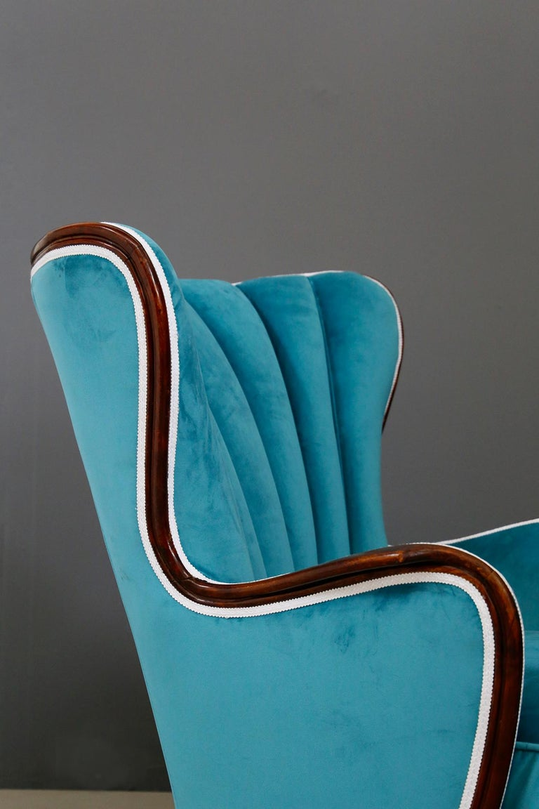 Elegant armchairs attributed to Paolo Buffa of the 1950s. The armchairs have been restored and re-lined in blue velvet fabric. The armchairs have many peculiarities but note the conical shaped feet in engraved wood. The shell-shaped upholstered