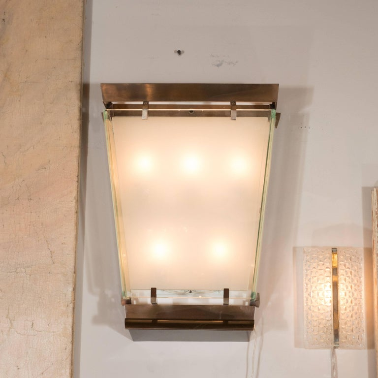This stunning pair of Art Moderne sconces were realized in France, circa 1950. They feature rectilinear patinated brass frames with L-shaped supports in the same materials. In the centre of each sits a frosted glass frame with translucent borders