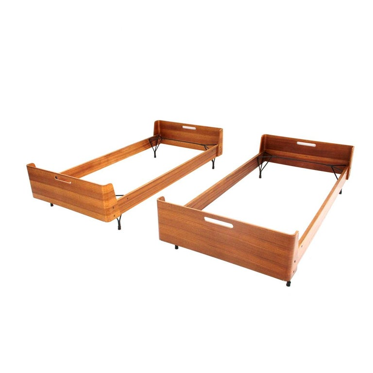 Pair of beds produced in the 1950s by Rima and designed by Gastone Rinaldi. Teak multi-layer structure with curved corners. Handle on headboard and footboard. Two bases in black painted metal. Good general condition, some signs and lack of