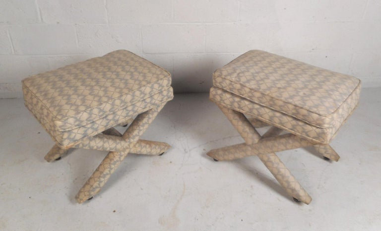 This pair of Billy Baldwin style ottomans feature a thick top cushion. These unique ottomans are versatile and can be used as stools or window benches. The pair of ottomans boast a plush and luxurious upholstery with a decorative pattern that would