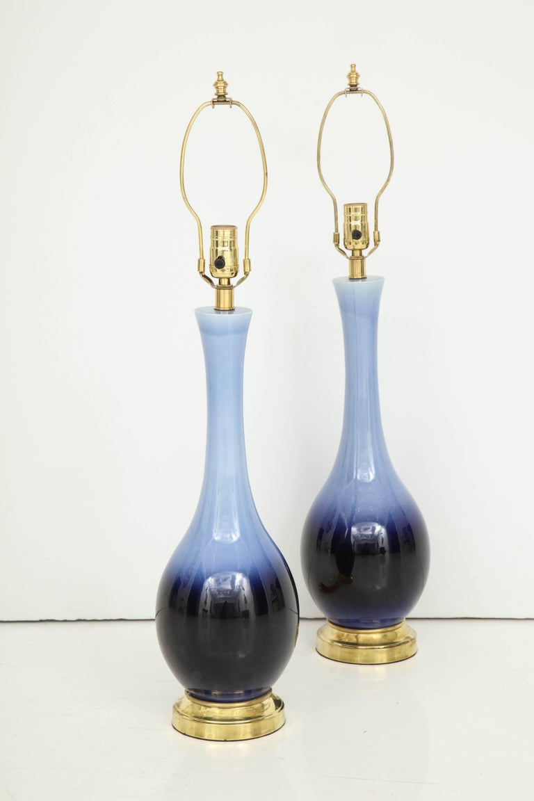 The blue glaze on these lamps transitions from a beautiful soft, pale blue to a deep indigo at the base. The urn shape lamps sit on a brass base and have brass fittings. Recently re-wired.