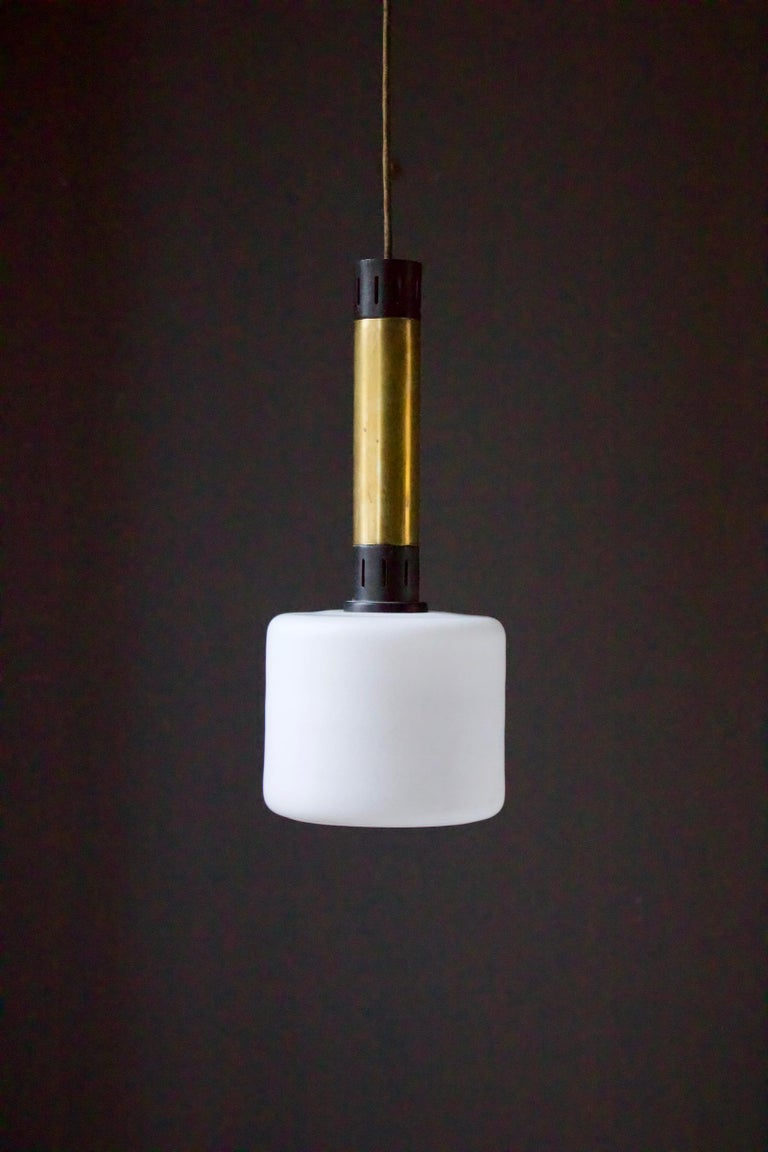 Pair of midcentury brass and satin glass pendant lights attributed Stilnovo, Italy.  The lights each comprise a large shade of white satin glass - which gives a good amount of light - topped with brass tubes and black-finished aluminium sections.