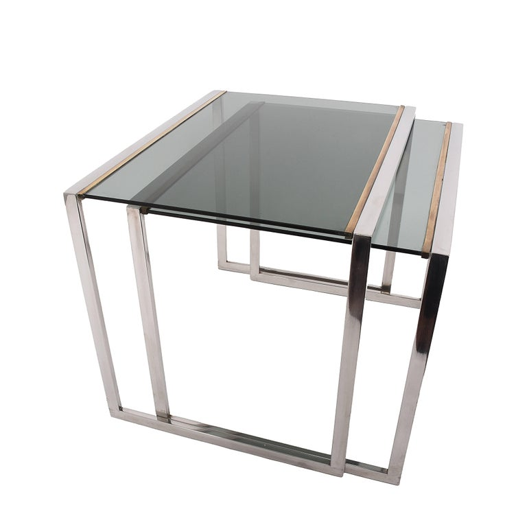 Mid-century modern Nesting tables in brass and crystal, France 1970s.  A very classic pair of nesting tables from the 70s, with smoked glass tops mounted between the two structure in brass. The result is elegant and simple, perfect for a