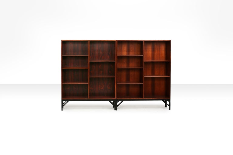 Set of two bookcases made of rosewood with a black lacquered base, designed by Børge Mogensen. Shelves on the inside are moveable. Manufactured and stamped by C.M. Madsen for FDB Møbler. 