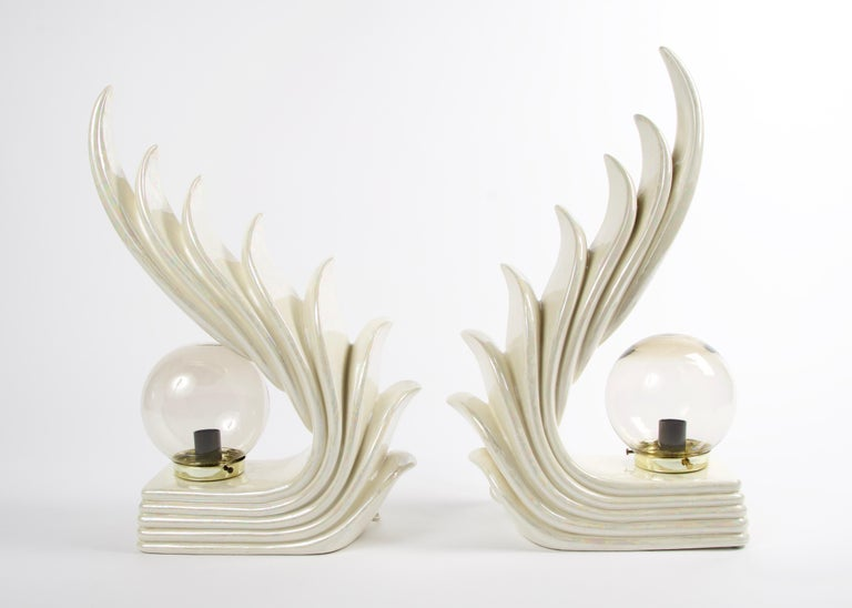 Stunning pair of Art Deco sculptural table lamps with a cascading wave design. These lamps have a cream ceramic glaze with an iridescent finish. The globes are a lightly smoked glass with a brass base. Due to them being handmade there are slight