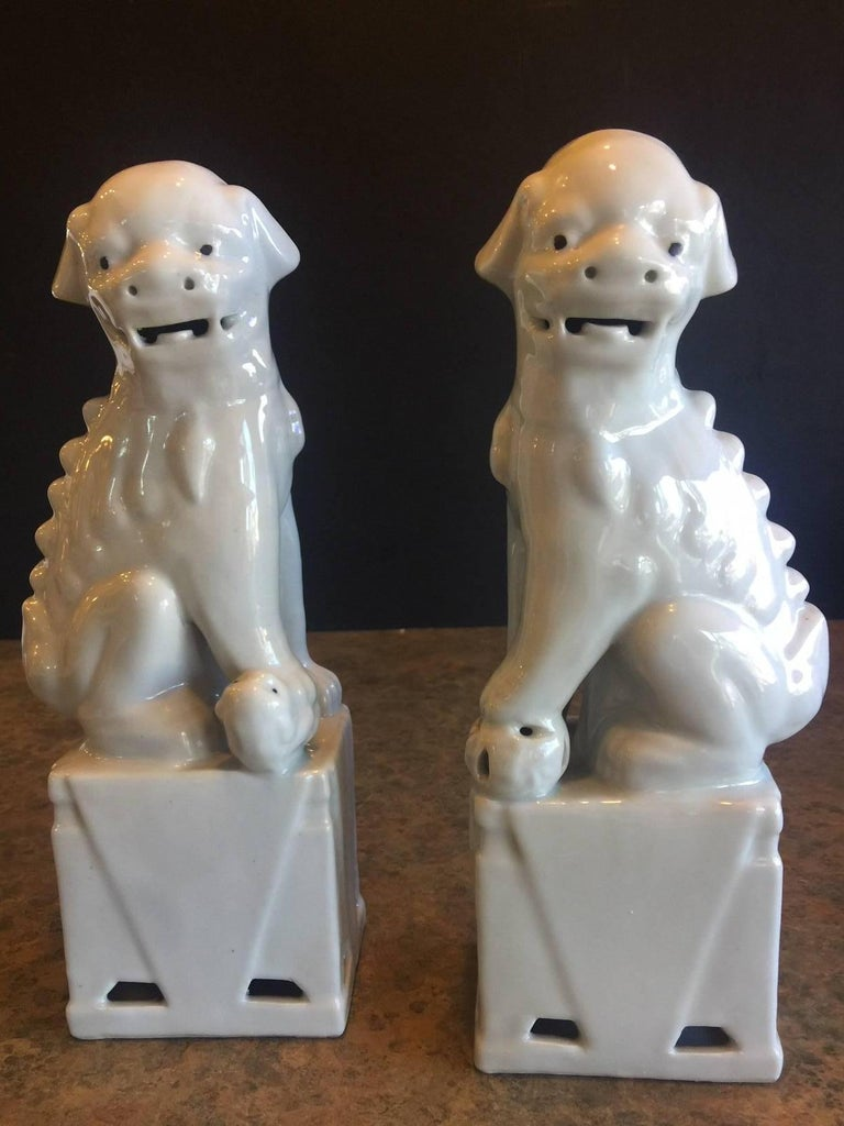 A very nice pair of Chinese, white, ceramic foo dogs, circa 1960s. Excellent condition and patina; makes a great pair of book ends or a fun decor item in any room!