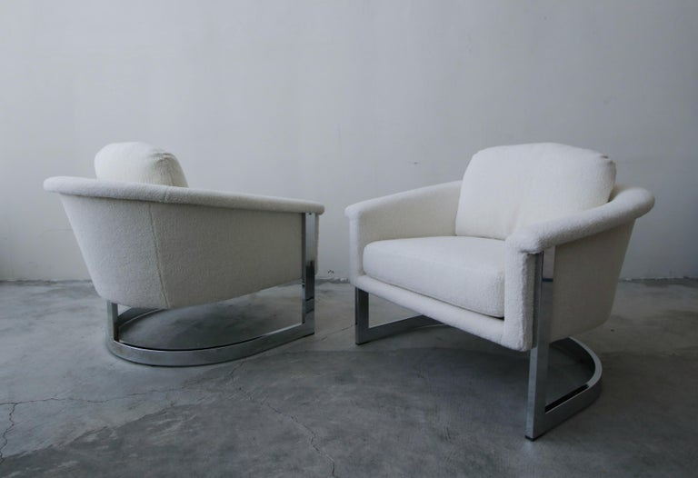 Exquisite pair of midcentury chromed steel, cantilever lounge chairs by Selig. They have a beautiful profile. The beautiful chrome frames cradle the chairs.   Chairs have been professionally restored with all new foam and faux Sherpa fabric. The