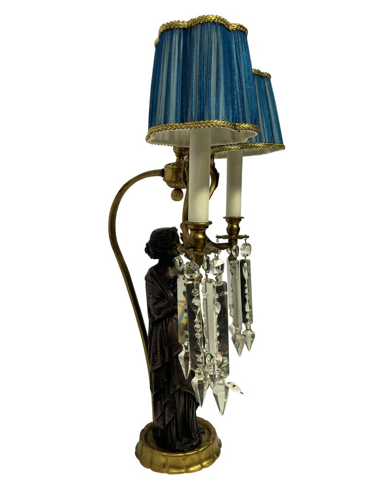 A pair of Italian Classical figural lamps depicting woman in Roman dress, each with cut glass pendant drops and with pale blue silk shades.