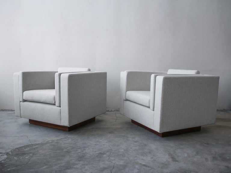 This is a gorgeous pair of midcentury cube lounge chairs with beautiful walnut plinth bases. The minimalistic style, clean lines a neutral upholstery make them the perfect addition to any decor.  The chairs have been professionally reupholstered