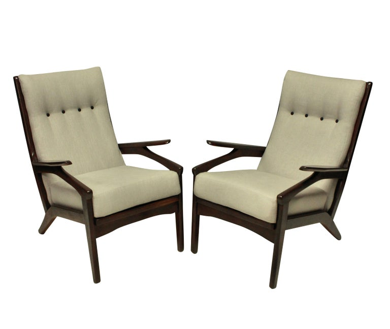 A pair of midcentury Danish armchairs in stained teak, which is a dark walnut in color. Newly upholstered in plain linen.