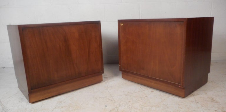 This beautiful pair of vintage modern nightstands feature two cabinet doors that open to unveil a large compartment for storage. Sleek straight line design with unique brass pulls, a finished back, and an elegant dark walnut finish. This stylish