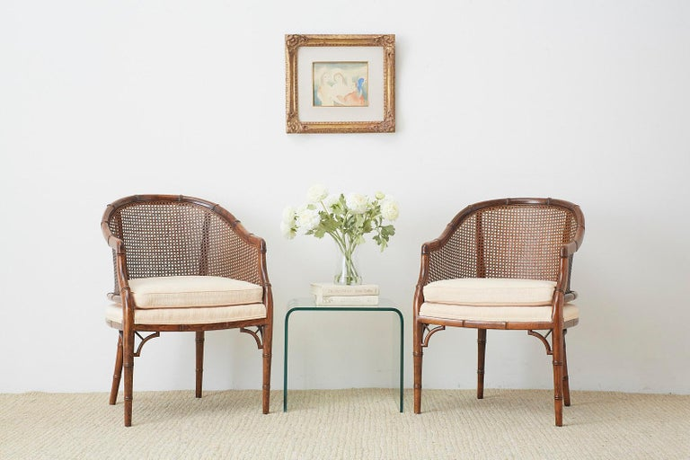 Exceptional pair of Mid-Century Modern barrel chairs by Century Furniture. Featuring a handcrafted faux-bamboo wooden frame with a caned back and sides. Made in the Hollywood Regency style with a loose seat cushion. Excellent joinery and finish from