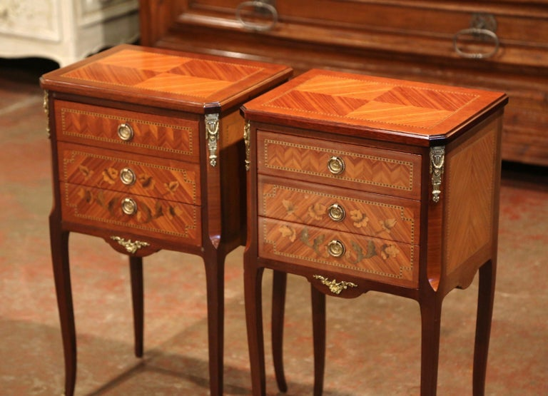 These elegant vintage bedside tables were created in France, circa 1950; each chest stands on cabriole legs with front sabots over a scalloped apron dressed with a bronze mount. The cabinet features three drawers decorated with floral marquetry