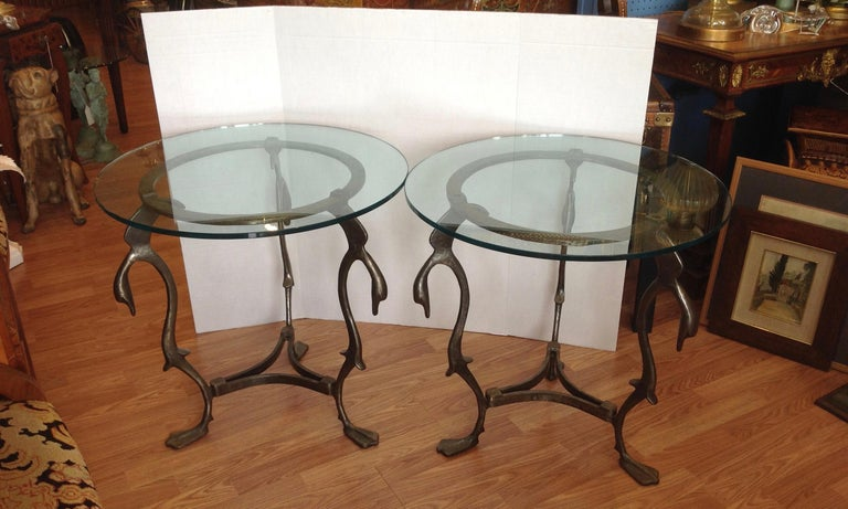 The tables are fashioned from steel and designed with 3 moderne swan form heads at the top; and terminate in web feet at their bases. The tables are mounted with glass tops.