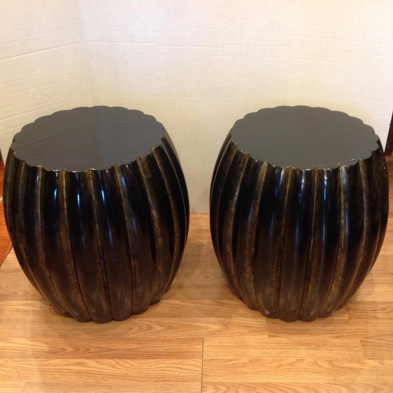Dramatic in scale and highly stylized with a rich black lacquer finish accented with gold highlights. The barrel form stands are fashioned with 20 vertical scallops.