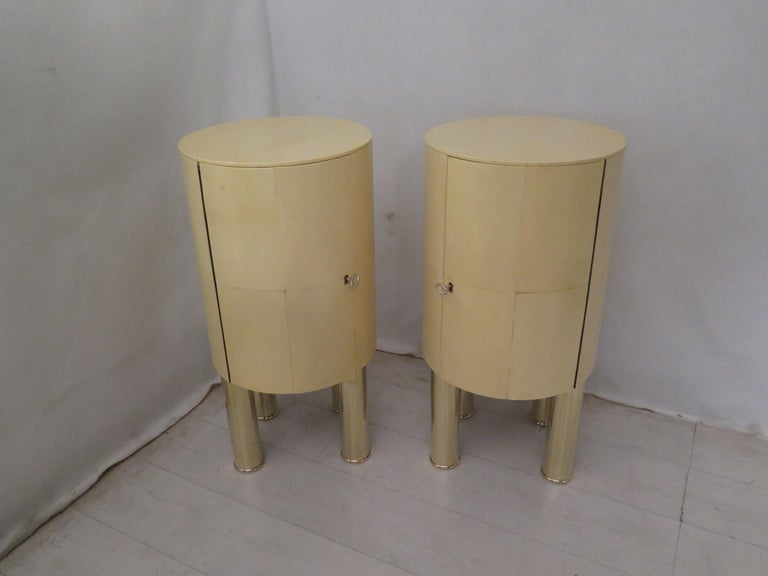 Original pair of bedside tables for the very special cylindrical design, and the use of sophisticated materials, goatskin and brass.  Their structure is in wood covered in goatskin. Cylindrical shape. They have a door on the front, with a large