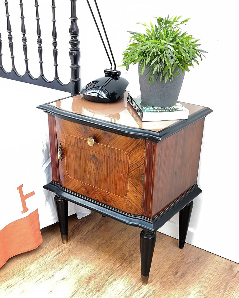 Very elegant and refined Italian 1950s Mid-Century Modern, neoclassical, in typical Art Deco midcentury design, pair of bedside tables in great walnut wood veneer craftmanship and inlay gilt decors with front top half drawer and half door, lacquered