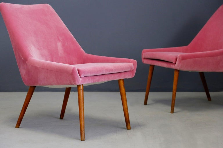 Pair of midcentury armchairs attributed to Italian designer Carlo Pagani from 1950. The armchairs have been restored and lined in pink velvet. Note the very long conical feet that give the seat a beautiful line. The peculiarity of the two armchairs