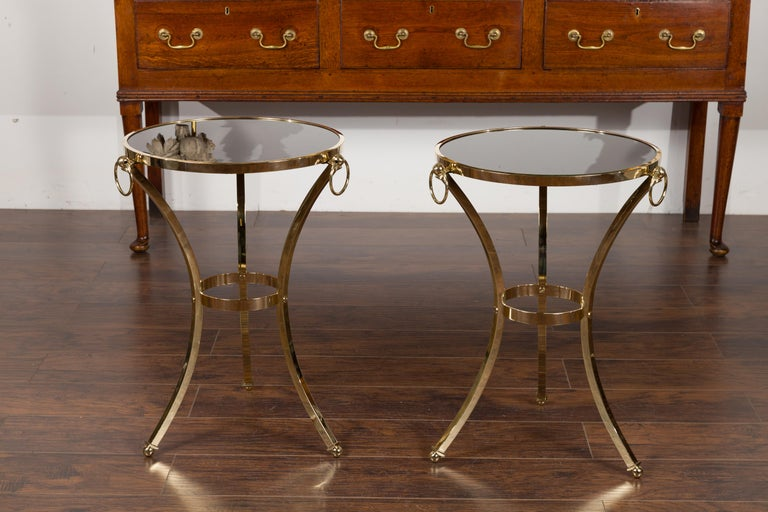 A pair of vintage Italian brass tables from the mid-20th century, with black mirrored tops and ring motifs. Created in Italy during the midcentury period, each of this pair of side tables features a circular round top showcasing a black mirror. The