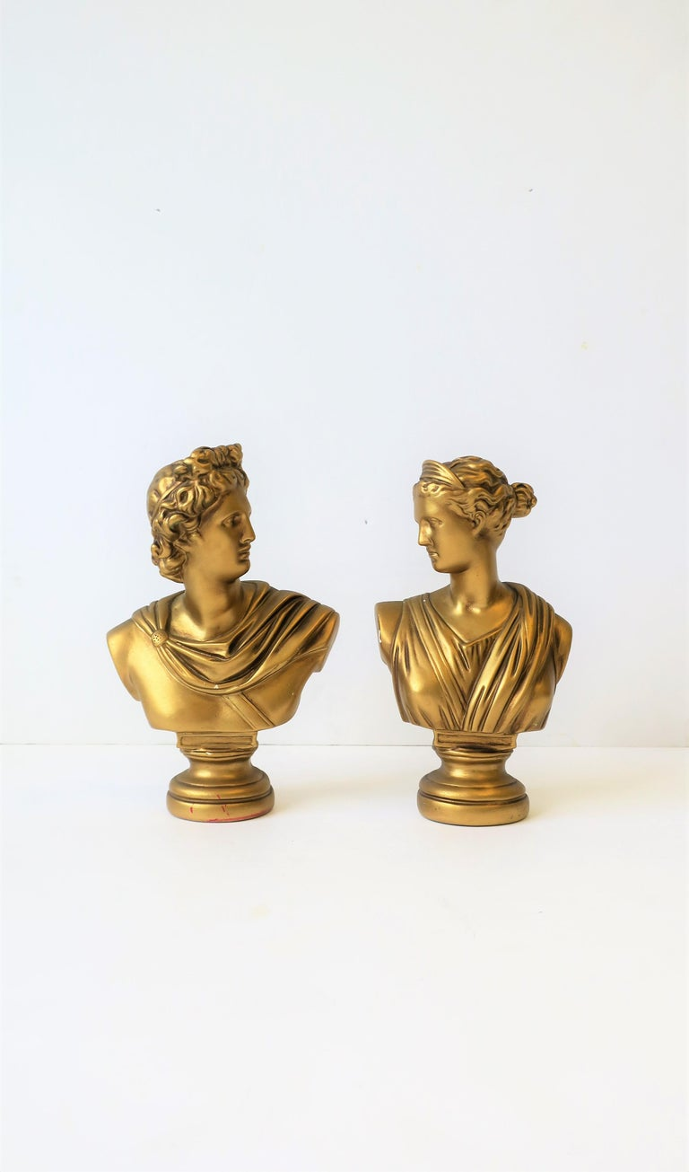 A beautiful pair of midcentury Italian male and female classical Roman style bust statue sculptures. Pieces are plaster with a gold overlay. 