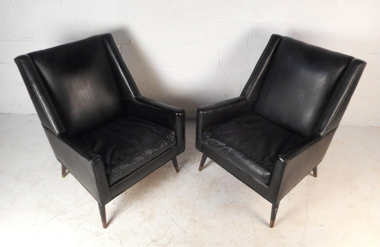 This pair of Italian lounge chairs are sure to add style to any seating arrangement. The chairs are covered in a soft dark vinyl upholstery with padded back rests and removable cushions for comfortable lounging. Beneath the chairs are splayed and