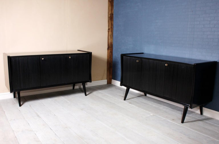 Pair of midcentury Italian piano lacquer sideboards These three reeded door sideboard are opposite pair one has fitted drawers with glass fronts the other has a dry bar They stand on splayed out legs and have inset brass locks, hinges and keys the