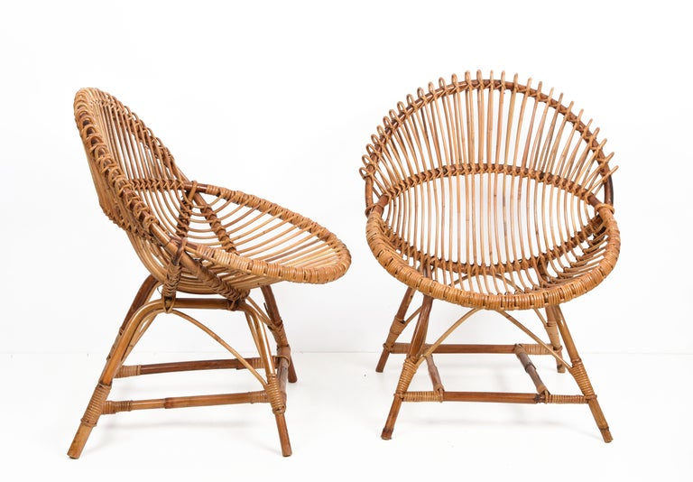 Amazing pair of midcentury rattan and black metal shell-shaped armchairs. These pieces were produced in Italy during 1950s and are attributed to Franco Albini.
