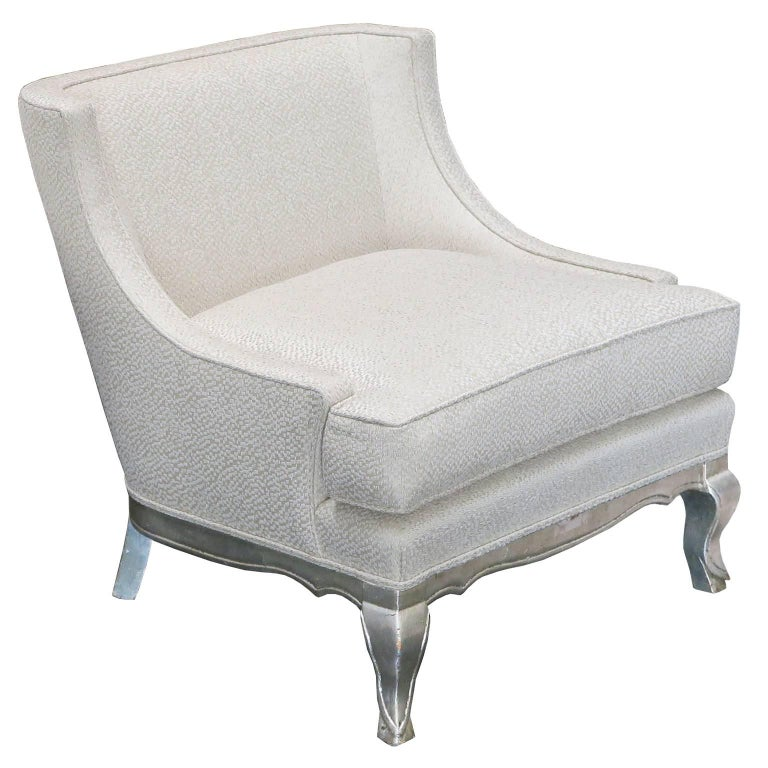 Elegant pair of lounge chairs with carved legs and base in distressed silver leaf. Curved arms with tight back and seat cushion are upholstered in ivory linen and silk fabric.