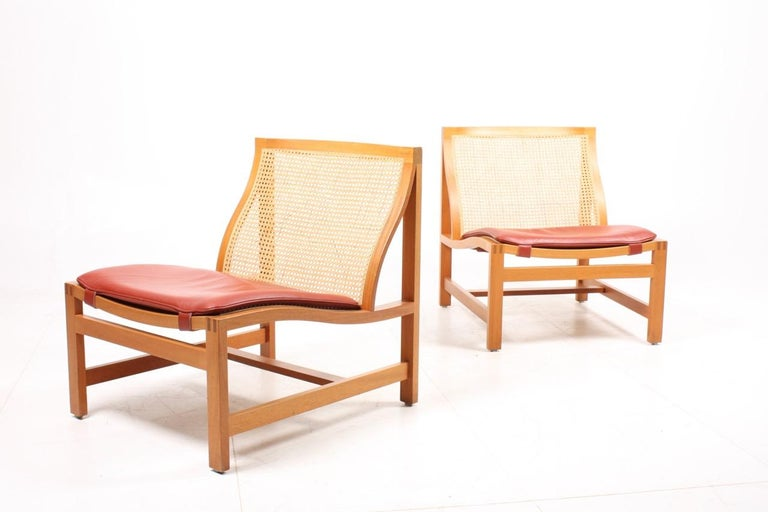 Pair of elegant lounge chairs with beech frame and French caning in seat and back. Seat cushion in patinated leather. Designed by Danish architects Johnny Sørensen and Rud Thygesen.
