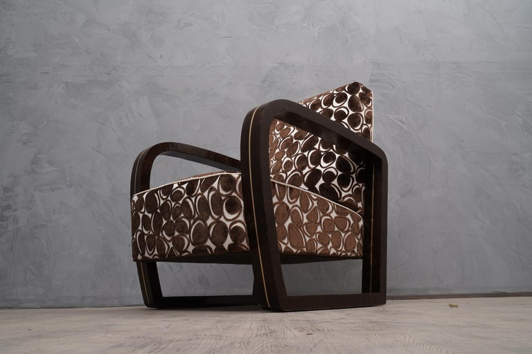 This pair of armchairs in addition to having a very original shape has been dressed with a very high quality velvet fabric. The combination of materials seems perfect, due to the use of materials such as Macassar wood and brass.