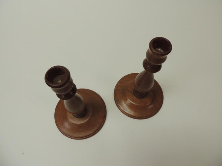 Pair of Mid-Century Modern round mahogany candleholders. Candlestick holder signed J W 1999. Size: 4.5 Base x 8 H.