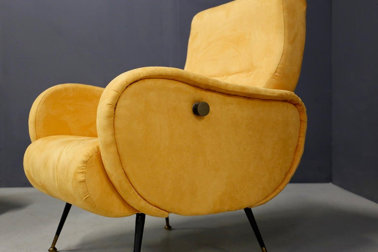 Pair of restored midcentury Italian armchairs from 1950. The armchairs are lined in yellow velvet. The particularity of the seats is their mechanism that makes the armchair reclining. Its mechanism is operated by a brass knob positioned on the sides
