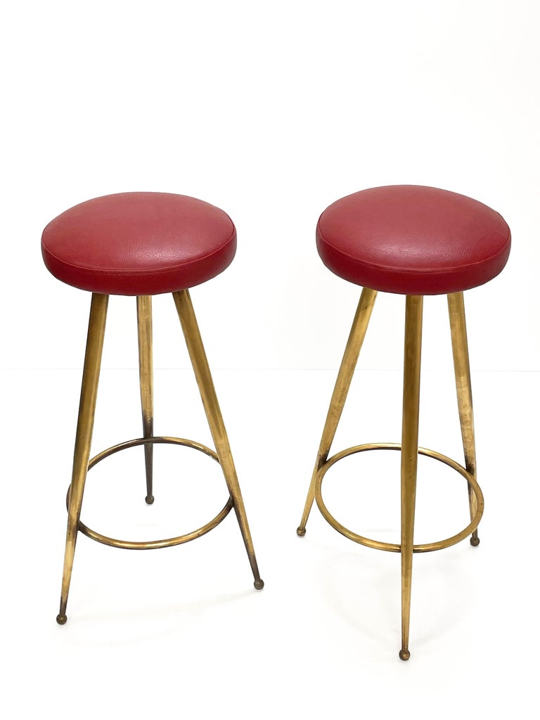 Magnificent pair of Mid-Century Modern bar stool in red vinyl and brass structure. This wonderful set was designed in Italy during the 1950s.  These pair of bar stools were constructed with three solid brass tapered legs on brass ball feet. The
