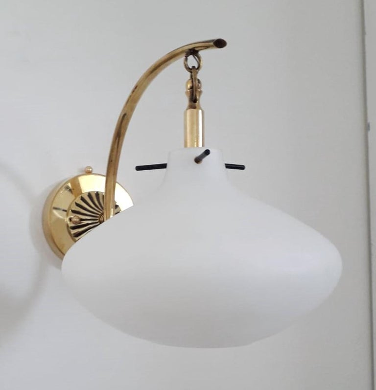 Vintage Italian wall lights with large pear shaped opaline glass diffusers suspended from curved brass frames resembling lanterns / Made in Italy by Stilnovo, circa 1950s. Measures: height 9.5 inches, width 8 inches, depth 14 inches 1 light / E12