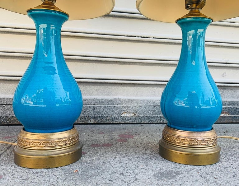 Vivid turquoise glazed ceramic lamps on brass bases, attb to Aldo Londi for Bitossi.The lamps are in very good original condition, they come with the original shade.  Measurements: 20.50 inches high to top of finial by 4.50 inches base diameter