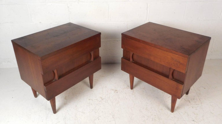 This beautiful Mid-Century Modern pair of nightstands offer plenty of room for storage within there two hefty drawers with sculpted fronts. Sturdy construction by American of Martinsville with a dark vintage walnut finish and tapered legs. Straight