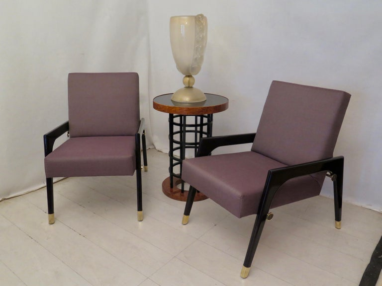 Pair of linear and simple armchairs in the architecture of their design, of the middle of the century, they are made valuable by simple tricks but very well finished.  The structure of the seat and backrest are covered with a Fine fabric; while