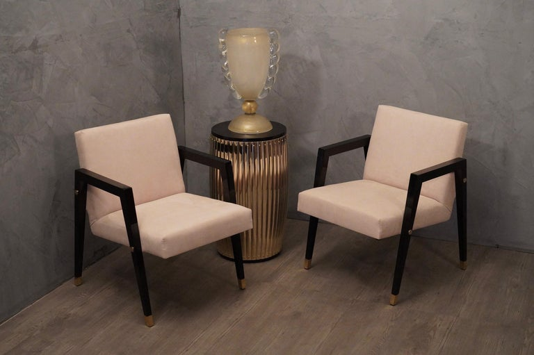 Pair of linear and simple armchairs in the architecture of their design, of the middle of the century, they are made valuable by simple tricks but very well finished.  The structure of the seat and backrest are covered with a fine white velvet