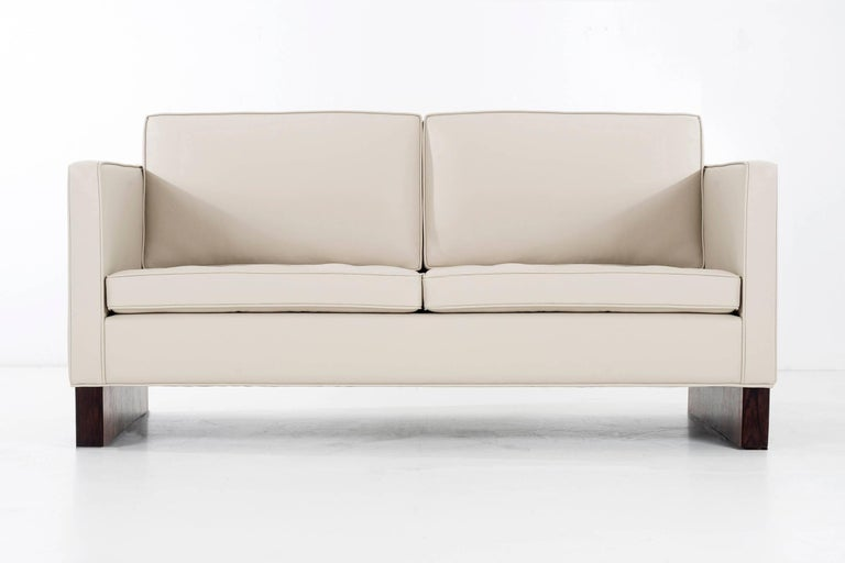 Mies for Knoll International settees, features rosewood plinth bases reupholstered in spinneybeck, tufted button seats and side bolsters. Retains original Knoll label on underside.